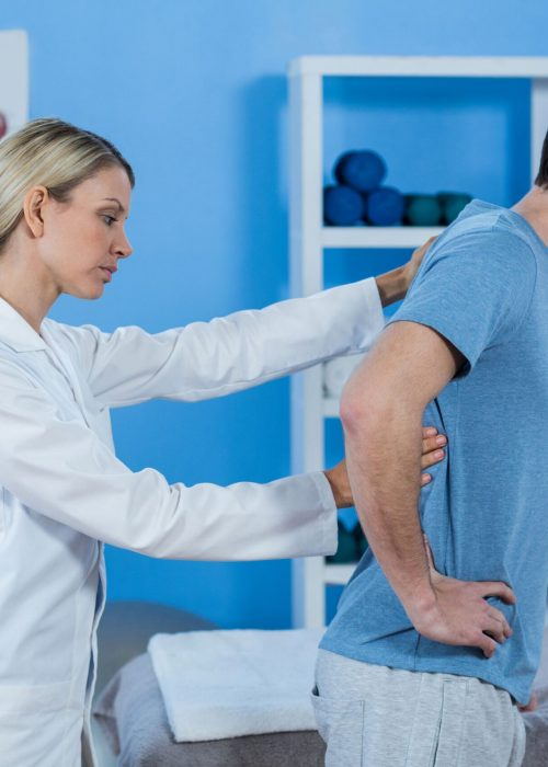 physiotherapist-examining-mans-back-HH4ZL6Z-min